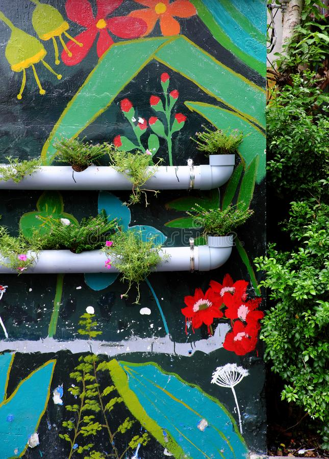 Flower pots from water pipes on wall with colorful painting background stock photos