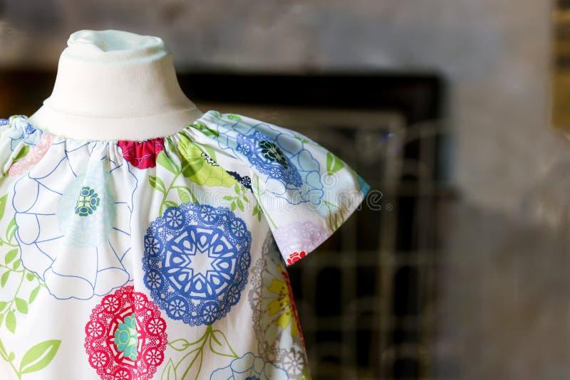 Flower power-Kinderkleid auf antikem Mannequin lizenzfreies stockbild