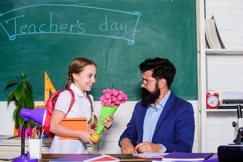 Flower present for best teacher. knowledge day is 1 september. small school girl kid with flower. back to school. Happy stock photo