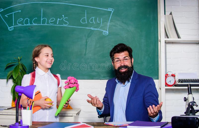 Flower present for best teacher. knowledge day is 1 september. teachers day. Daugghter and father with flowers. small. School girl kid with flower bouquet. back stock image