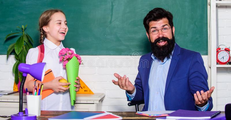 Flower present for best teacher. teachers day. Daugghter and father with flowers. small school girl kid with flower. Bouquet. knowledge day is 1 september. back royalty free stock image