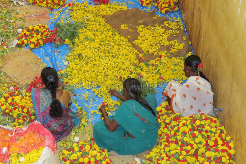 Flower sellers in KR market,Bangalore. Sorting out flowers in KR market stock image