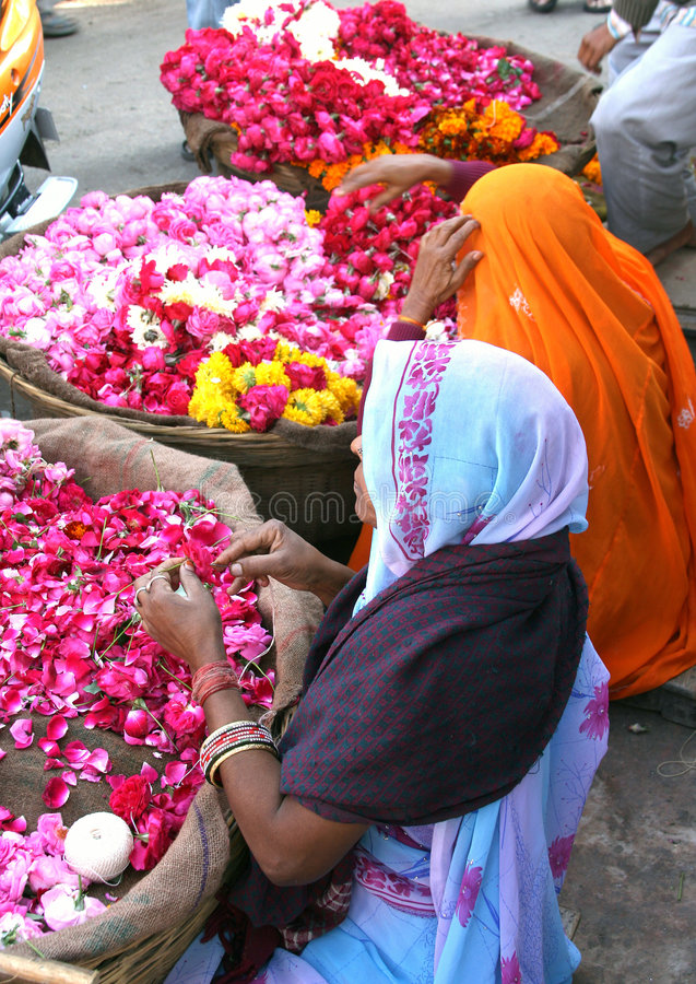 Flower sellers in Pushkar, India. Ladies in colorful clothing selling flowers at a market in Pushkar, India royalty free stock photography