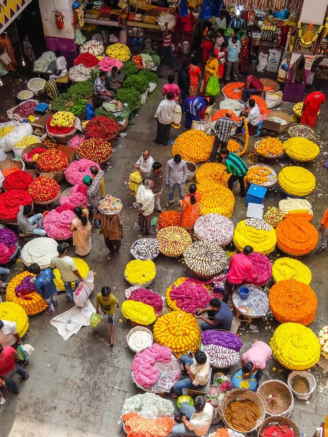 Flower sellers and their customers at colorful KR Market in Bangalore. Bangalore, India - Circa January, 2018. Flower sellers and their customers at colorful KR stock photography