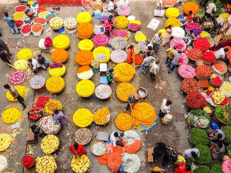 Flower sellers and their customers at colorful KR Market in Bangalore. Bangalore, India - Circa January, 2018. Flower sellers and their customers at colorful KR stock image
