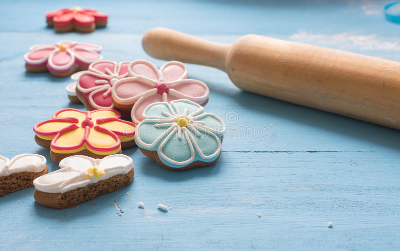 Flower shaped gingerbread cookies and rolling pin on a blue wooden table. stock photos