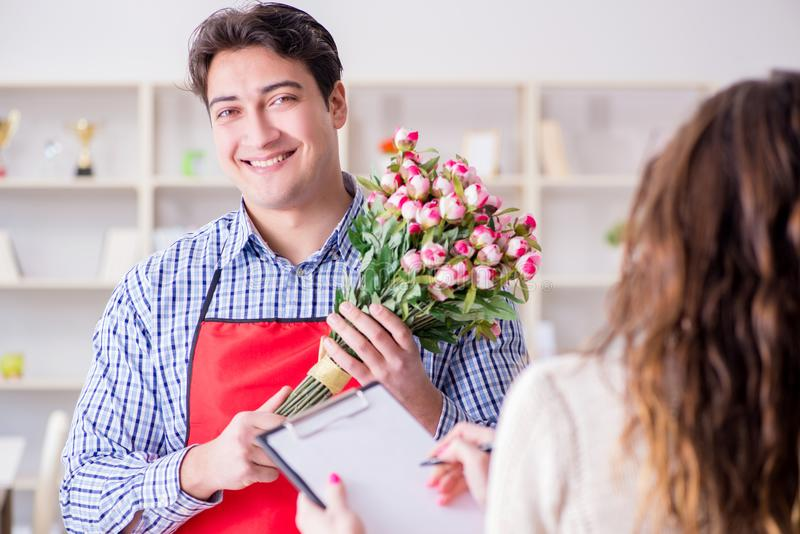 The flower shop assistant selling flowers to female customer royalty free stock photography