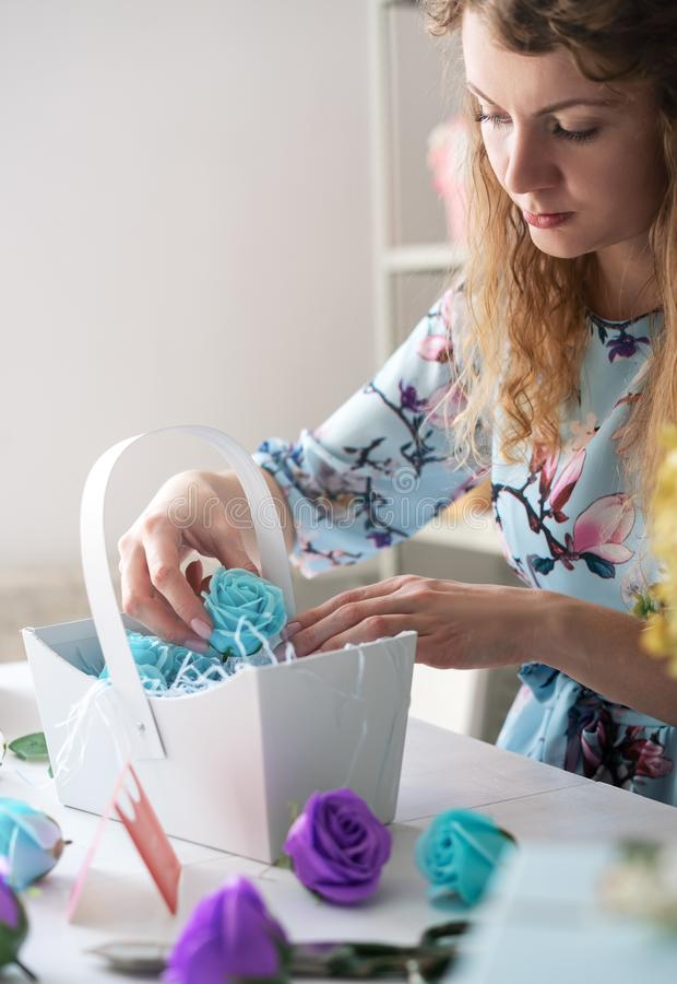 Flower shop: florist girl collects a bouquet of red roses in a blue paper basket. Close-up royalty free stock photography