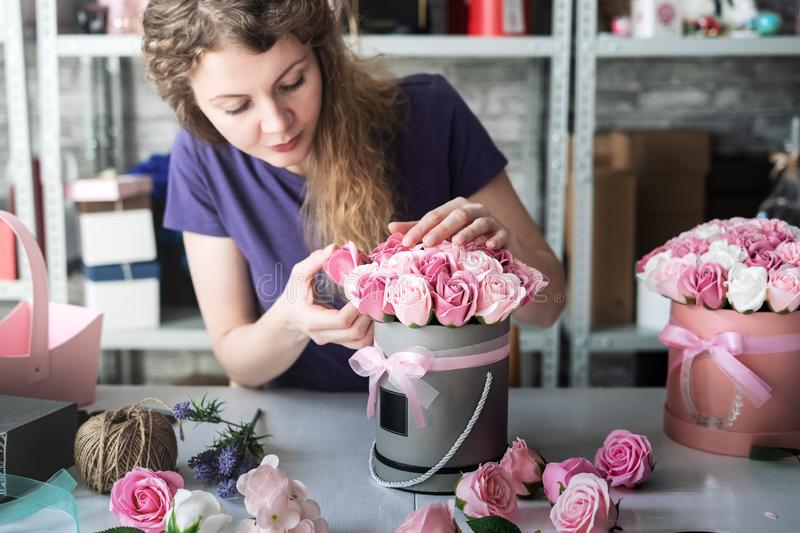 Flower shop: a florist girl collects a bouquet in a round box of pink roses. Blond curly hair, gray background. Flower shop: a florist girl collects a bouquet stock photo