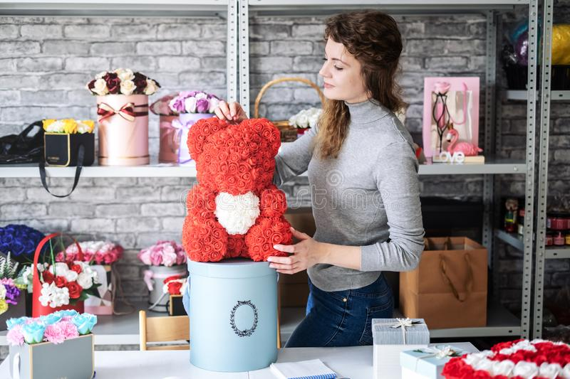 Flower shop: Florist girl shows a teddy bear of small red roses. Around the workshop and a lot of different floral. Bouquets. Portrait royalty free stock photos