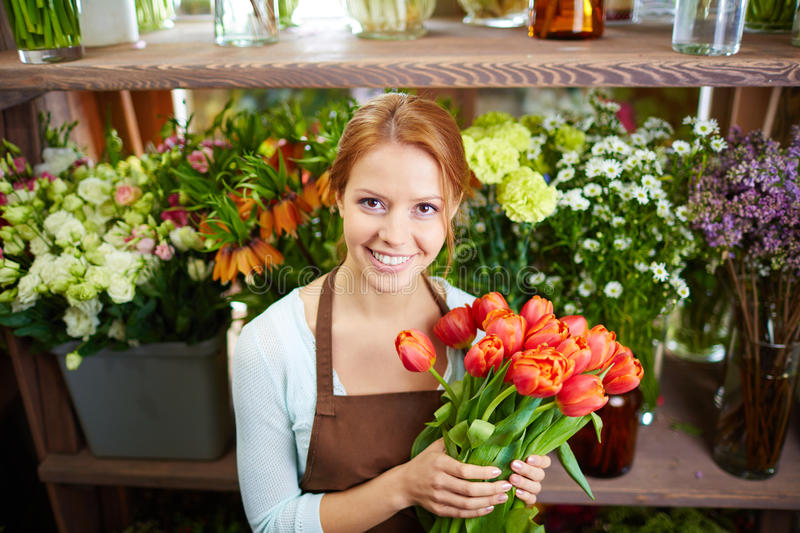 In flower shop. Smiling woman with flowers standing at flower shop royalty free stock photos