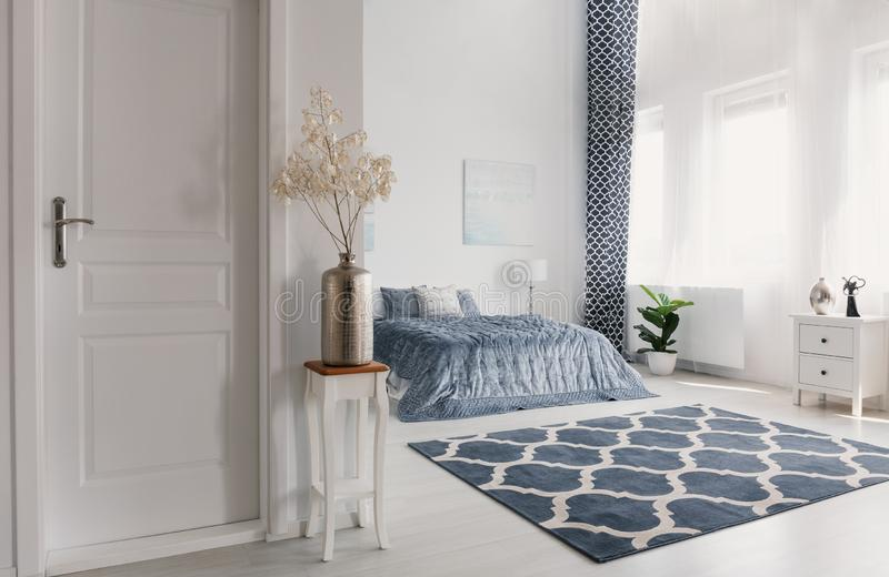 Flower in silver vase on the wooden table next to closed door to elegant new york style bedroom with patterned carpet and white fu. Rniture, real photo concept royalty free stock images