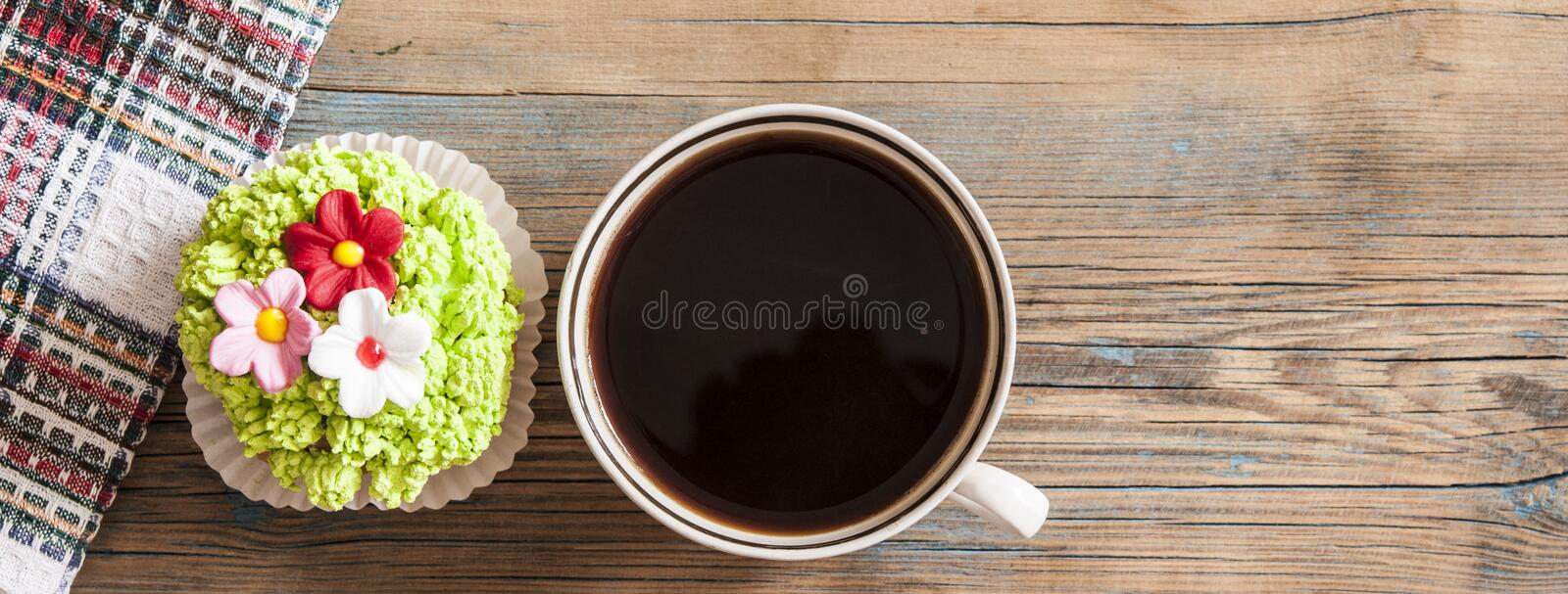 Flower spring cupcake with hot coffee cup on wooden table stock images