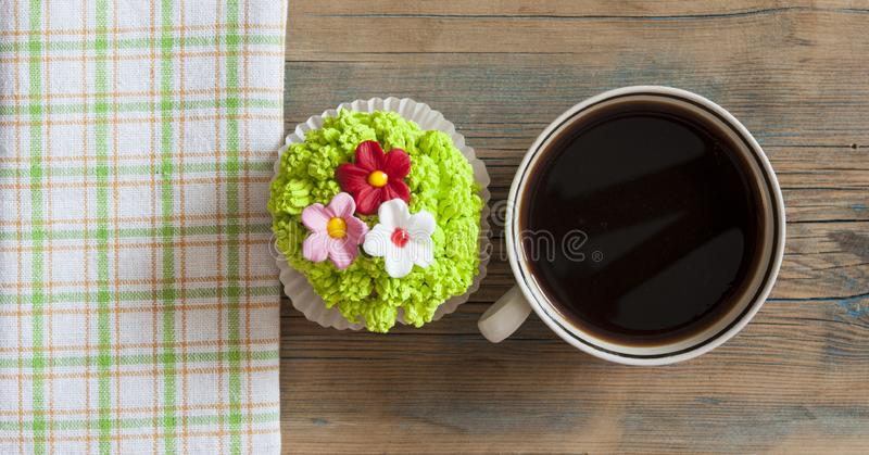 Flower spring cupcake with hot coffee cup on wooden table royalty free stock image