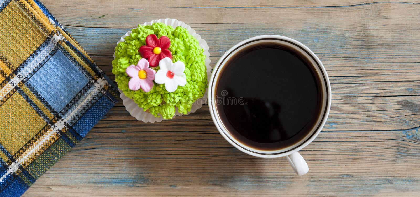 Flower spring cupcake with hot coffee cup on wooden table royalty free stock photo