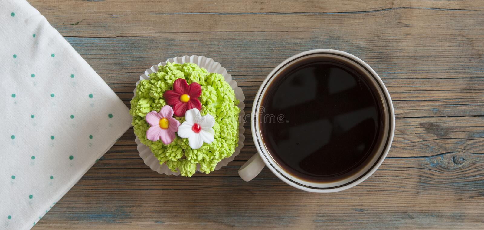 Flower spring cupcake with hot coffee cup on wooden table stock photography