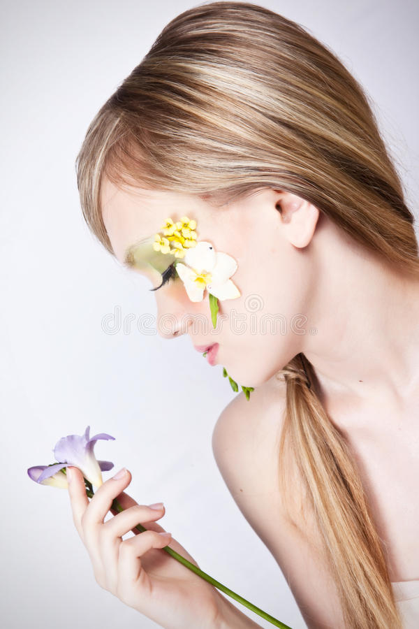Flower spring face art profile portrait. Studio white background portrait of a beautyful blond girl with face art and spring flowers in hair and on face royalty free stock image