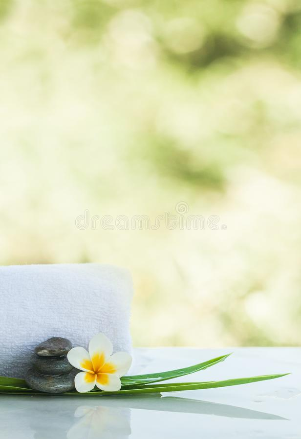 Flower and stones for massage treatment. On white light background stock image