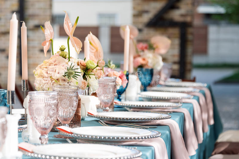 Flower table decorations for holidays and wedding dinner. Table set for holiday, event, party or wedding reception in. Outdoor restaurant royalty free stock images