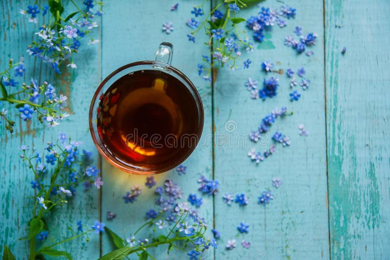 flower tea and a bouquet of forget-me-nots on a wooden background royalty free stock photos