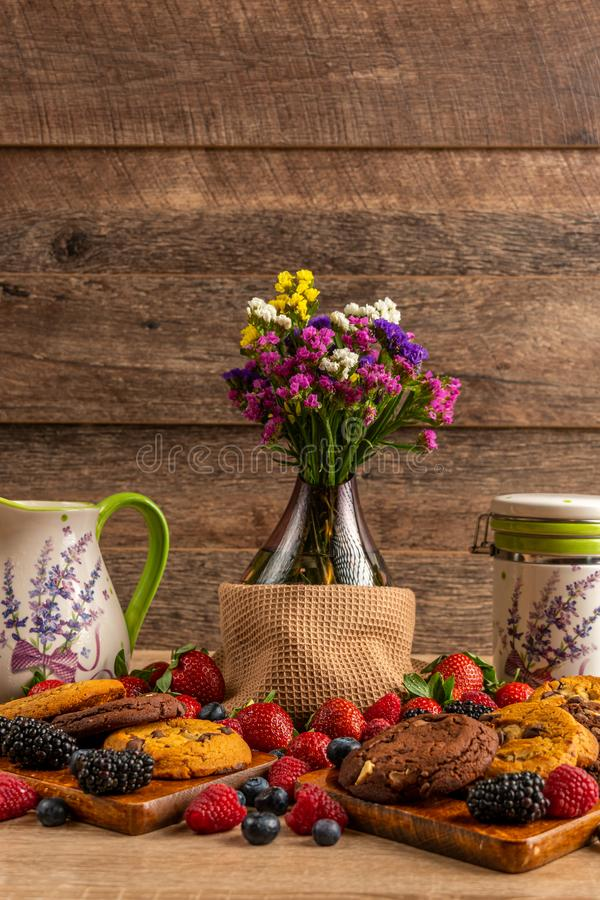 Flower vase, ceramic vessels with assorted mix of wild fruits and cookies stock photo