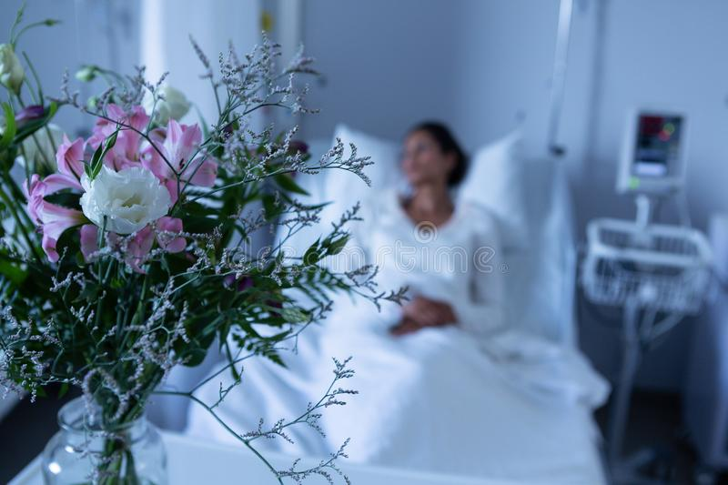 Flower in a vase on table in front of hospital bed stock photo