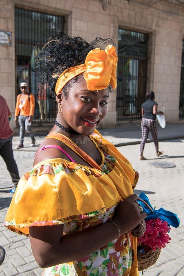 Beautiful street entertainer - flower girl in traditional costume, Havana, Cuba royalty free stock image