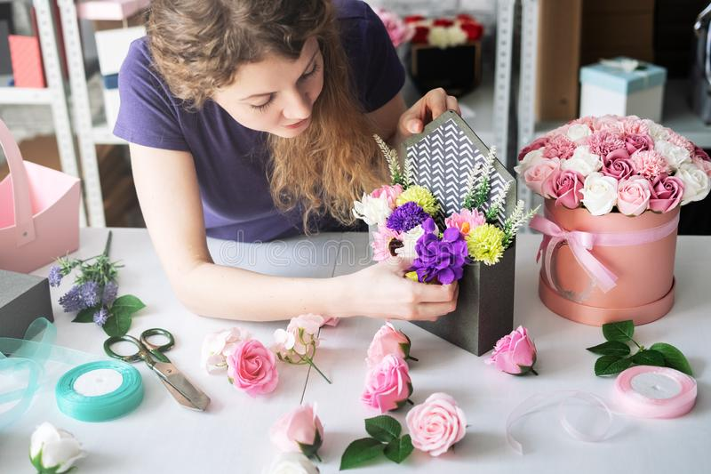 Flower workshop: a girl florist assembles a bouquet of colorful flowers to order in a purple envelope box. Close-up stock photography