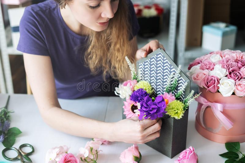 Flower workshop: a girl florist assembles a bouquet of colorful flowers to order in a purple envelope box. Close-up royalty free stock photo
