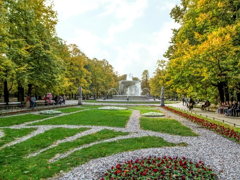Flowerbeds with a fountain in the Saxon Garden in Warsaw Poland on an autumn sunny day. Beautiful scenery of the oldest public. Park in the center of the Polish stock image