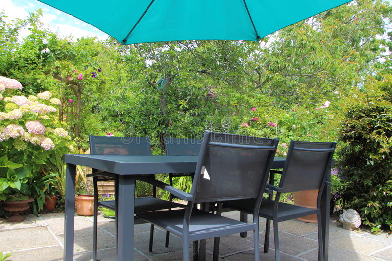 Flowered terrace with garden furniture stock photography