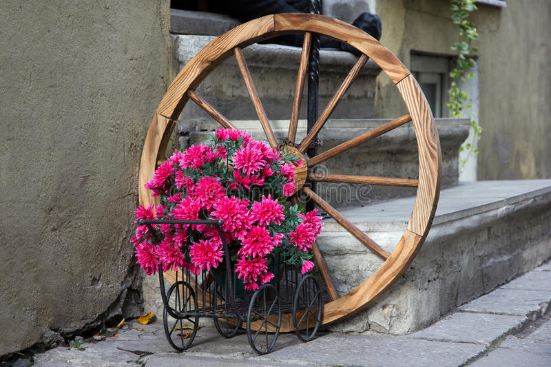 Flowered wagon with antique old wheel stock images