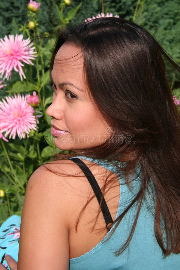 Flowergirl in profile. Beautiful brunette sitting in the garden among flowers a lovely summerday in Sweden stock photos