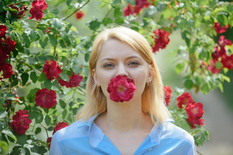 Flowering beauty. Adorable girl with flower bloom. Pretty girl at blossoming rose bush. girl with red flowers in stock photos