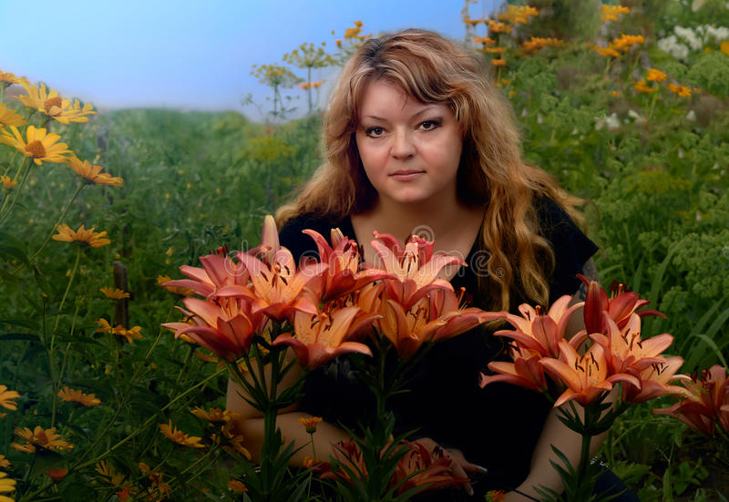 Flowering of life-beautiful young woman in the garden sits among flowers royalty free stock image
