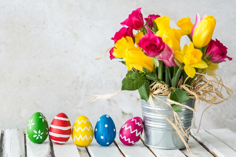 Flowerpot with flowers. Metal flowerpot with colorful flowers next to easter eggs stock photos