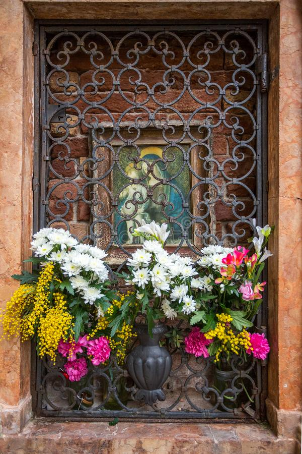 Flowers in an Alcove. Venice, Italy - March 1, 2015: Fresh and colorful flowers sit in an alcove on a street in Venice, Italy stock photography
