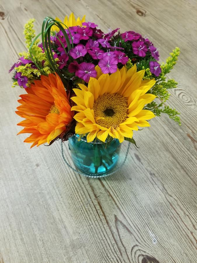 Colorful flowers in a blue glass jar royalty free stock image