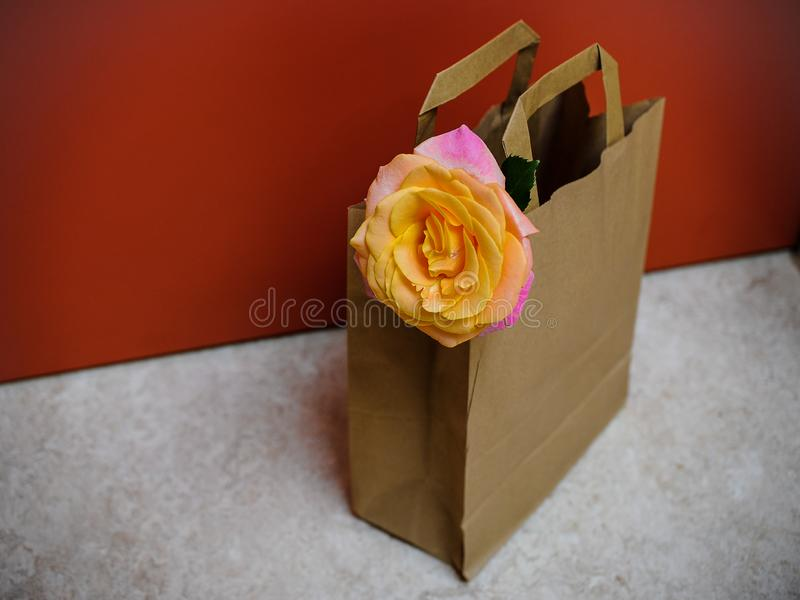 Valentines Nice idea , remarkable way to say I love you - a single rose in a paper bag on the floor in front of a door at a hotel royalty free stock image