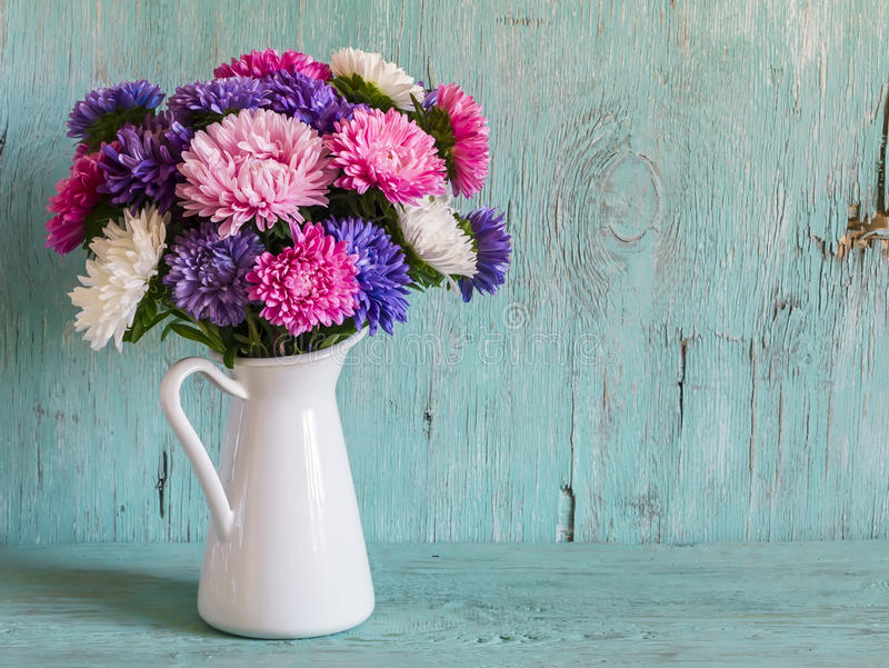 Flowers asters in white enameled pitcher royalty free stock photo