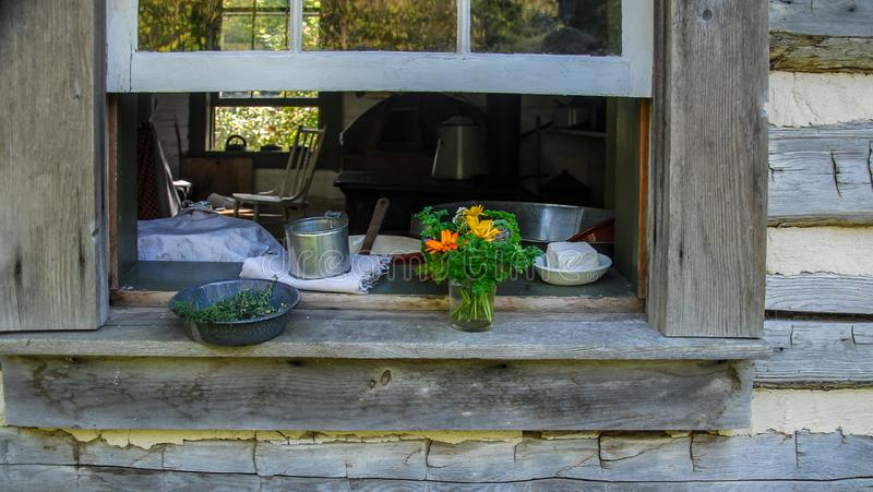Flowers and Baked Goods by Open Window of an Old Cabin. Beautiful summer flower bouquet, herbs and baked goods by an open window of old cabin at Old World royalty free stock photo
