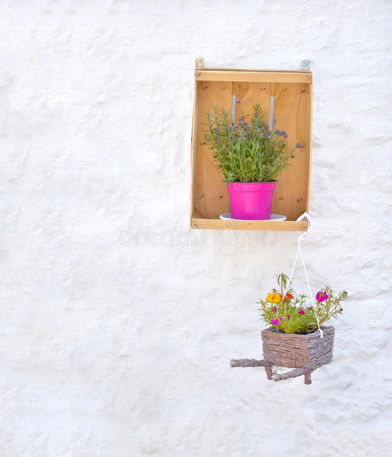 Flowers and baskets against white painted brick wall in Alberobello italy stock image