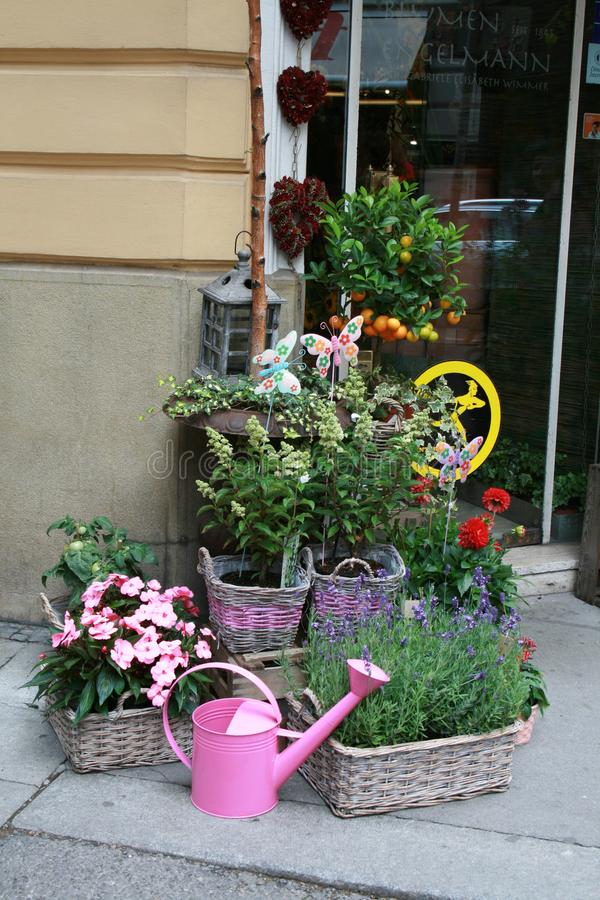 Flowers in baskets and a watering can at the entrance royalty free stock photography