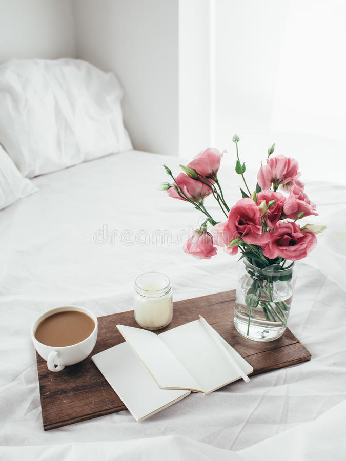 Flowers in bed, good morning concept. Wooden tray with paper sketchbook, candle and spring flowers on clean white bedding. Good morning concept stock photos