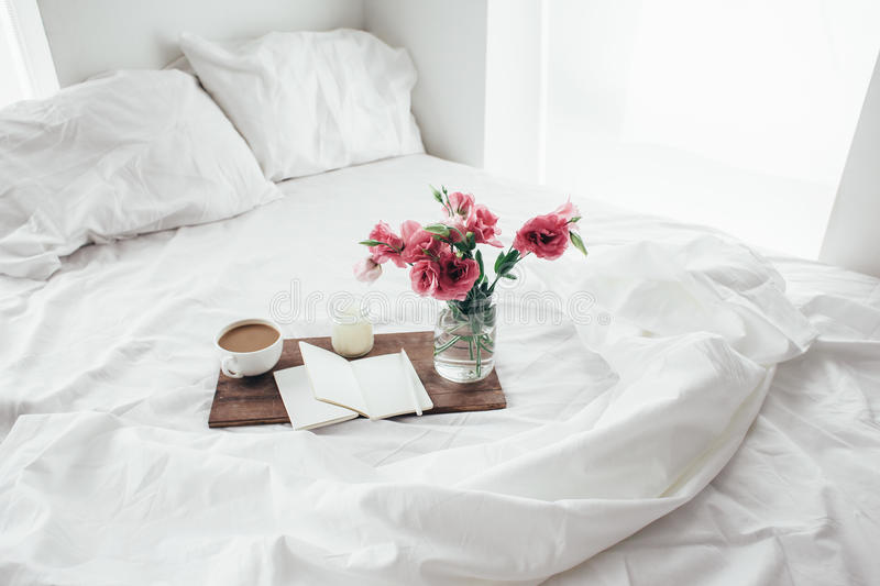 Flowers in bed, good morning concept. Wooden tray with paper sketchbook, candle and spring flowers on clean white bedding. Good morning concept royalty free stock image