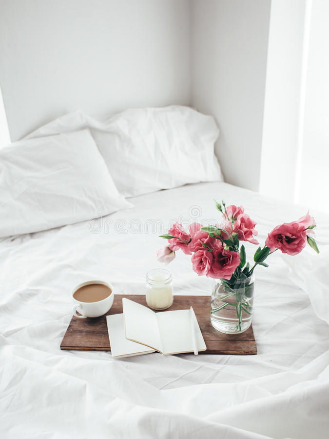 Flowers in bed, good morning concept. Wooden tray with paper sketchbook, candle and spring flowers on clean white bedding. Good morning concept royalty free stock photography