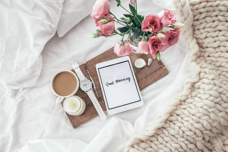 Flowers in bed, good morning concept. Wooden tray with tablet, coffee and spring flowers on clean white bedding. Good morning concept stock images