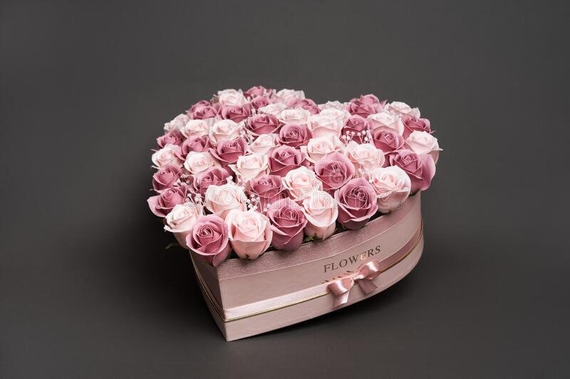 Flowers in bloom: A large bouquet of pink and white roses in a box in the shape of a heart on a gray background. Closeup with details of buds and petals stock images