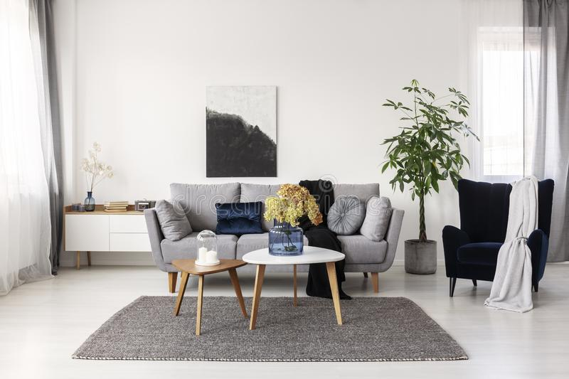 Flowers in blue glass vase and two white candles on wooden coffee tables in grey elegant living room with comfortable sofa. Flowers in glass vase and two white stock images