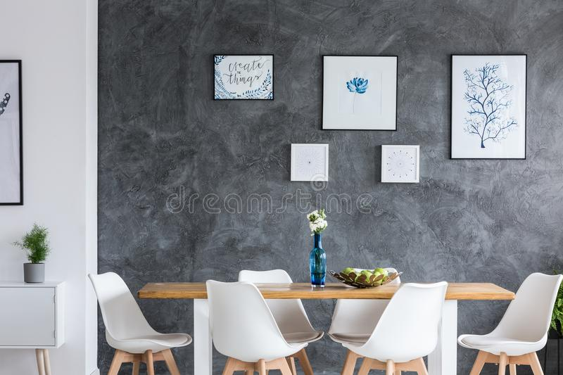 Monochromatic dining room with gallery. Flowers in blue glass vase on wooden table in monochromatic dining room with gallery on wall stock images